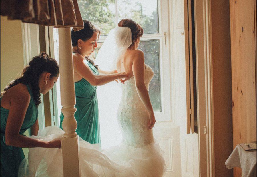 Irish weddings, bridal prep photo, bridesmaids helping, golden light