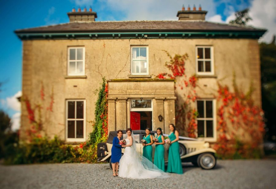 Irish weddings, bride & bridesmaids with mother, antique car, blue sky, old house
