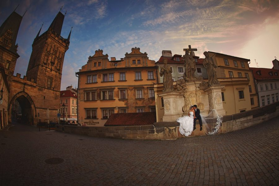 Prague Charles Bridge at sunrise, wedding portrait, sitting under statue, sky flaring, wide angle