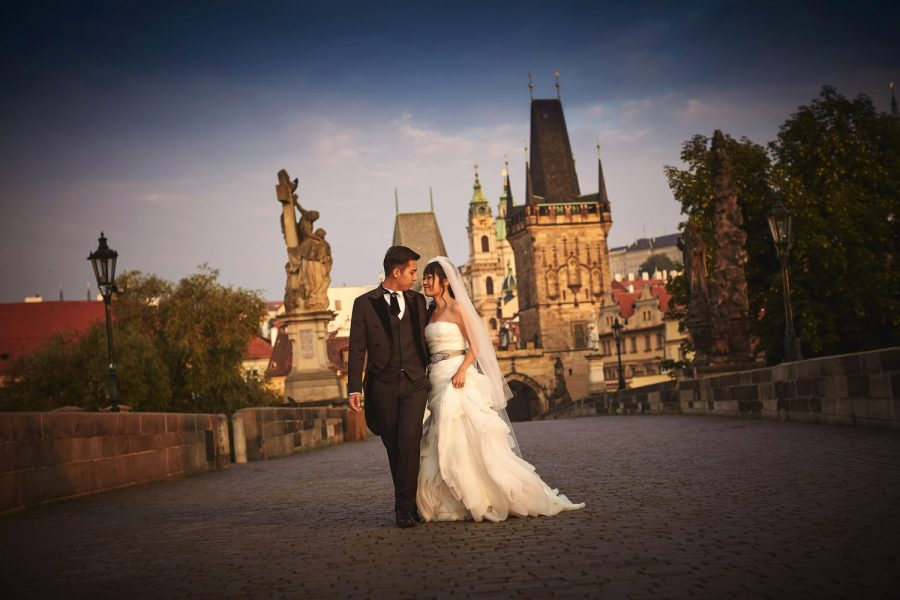 Prague Charles Bridge at sunrise, wedding couple walking, smiling, blue sky