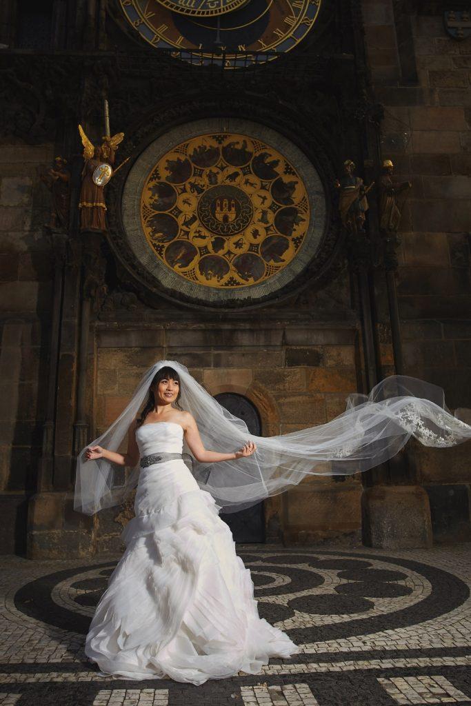 Prague Old Town, bridal portrait, blowing veil, Astronomical Clock, happy bride
