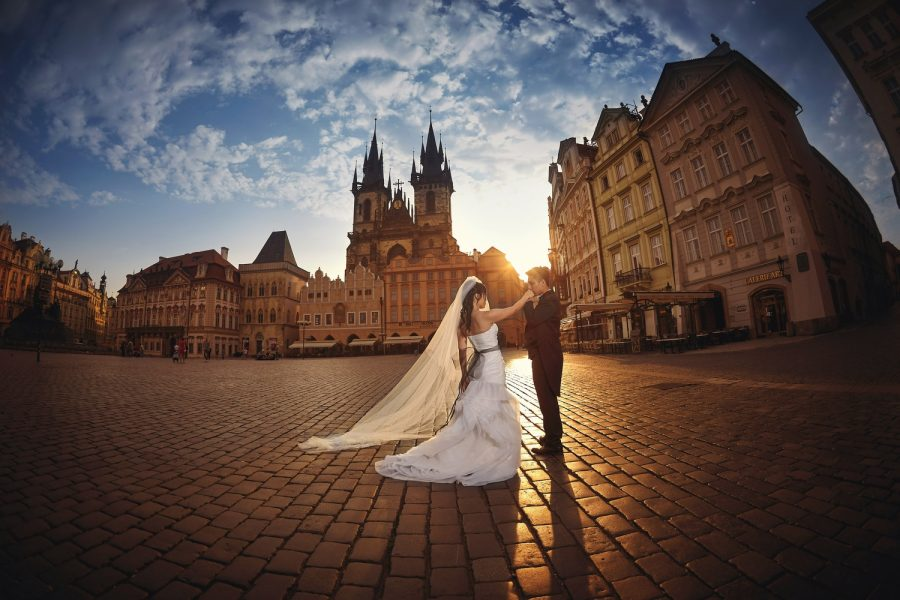 Prague Old Town Square, wedding couple, kissing her hand, sun flare, wide angle photo, dramatic sky
