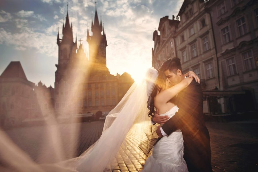 Prague Old Town Square, wedding couple, embracing, sun flare, wide angle photo, veil, dramatic sky