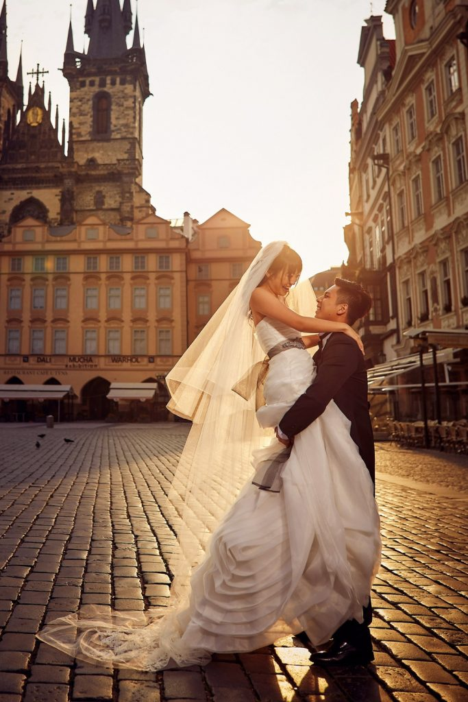 Prague Old Town Square, wedding couple, holding her up high, sun flare, white wedding dress