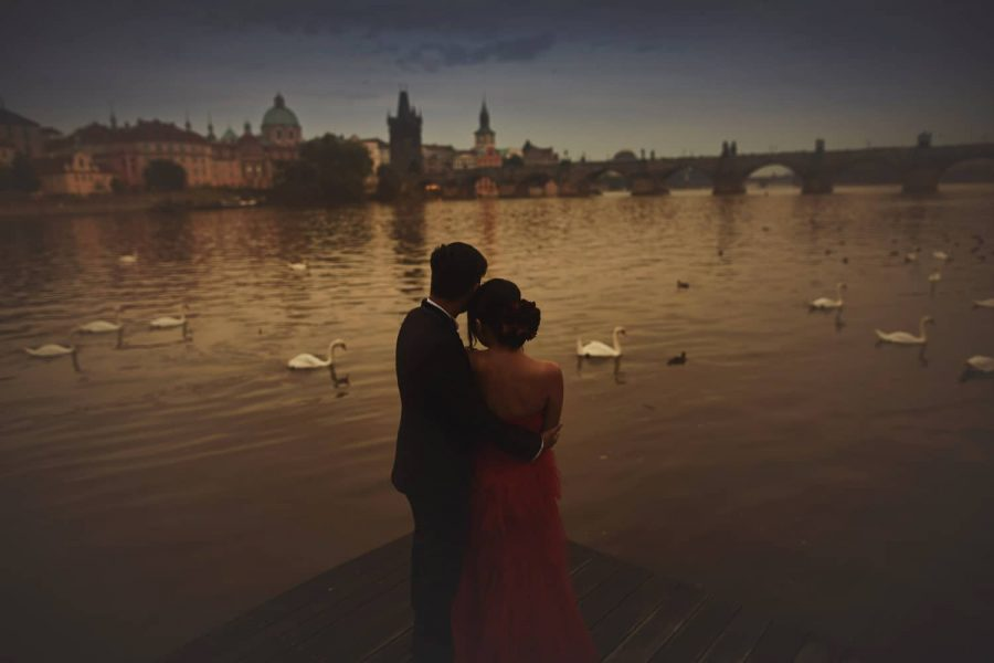 Prague, Charles Bridge, riverside, moody, swans, couple embracing over the water
