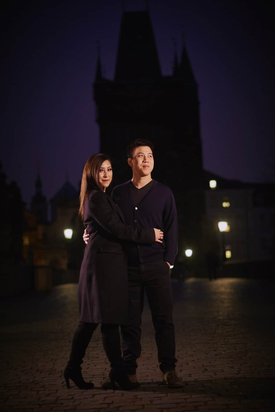 Prague Charles Bridge at night, stylish young couple wearing black, holding each other