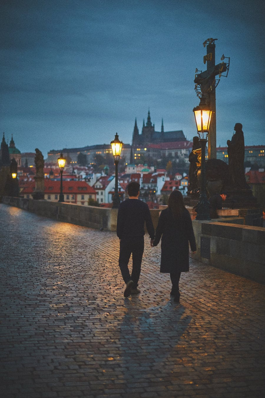 Prague Charles Bridge, dark blue sky, stylish young couple walking wearing black, gas lamps