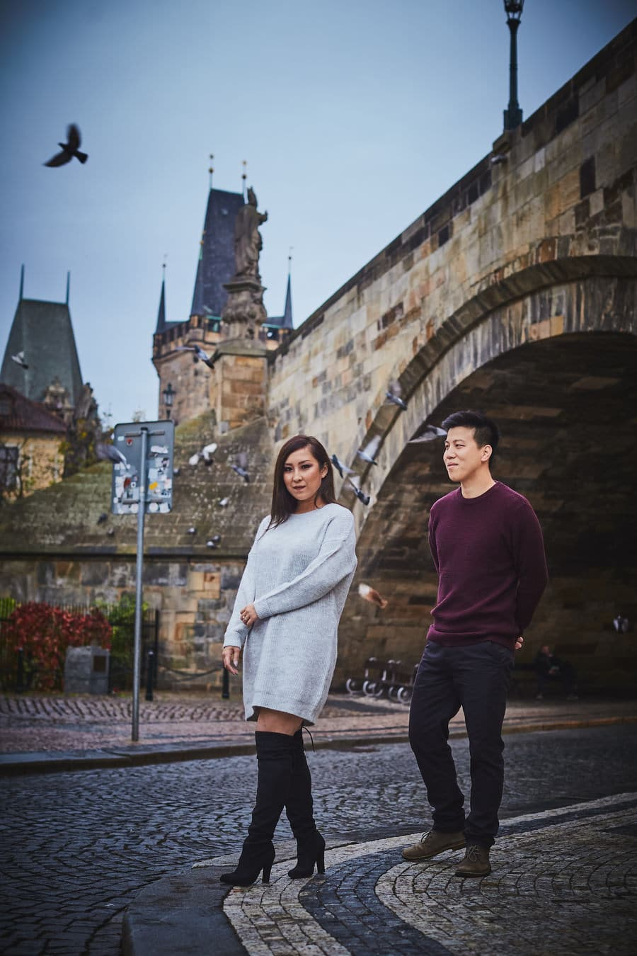 Prague Charles Bridge, stylish young couple posing, birds flying, blue sky