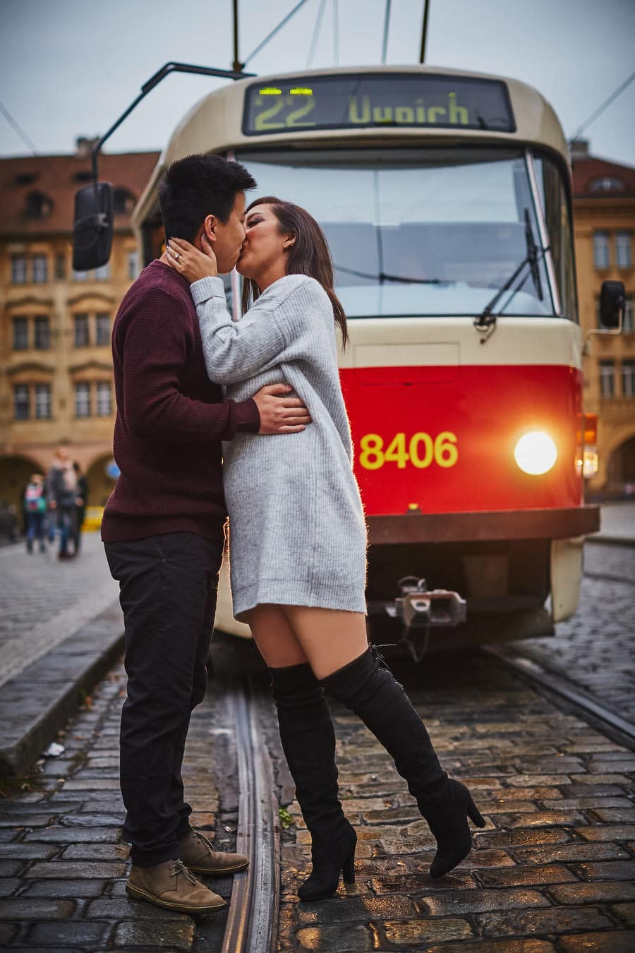 Prague, stylish young couple kissing in front of tram with lights on