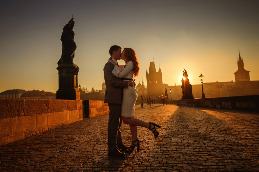 Prague Charles Bridge sunrise, Golden & Orange color, sun flare, moody, couple embracing