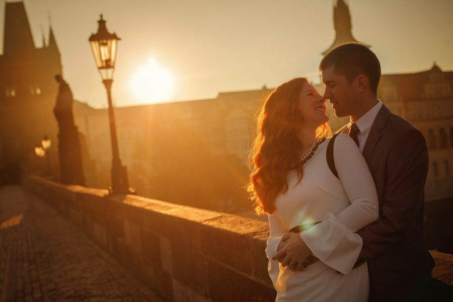 Prague Charles Bridge sunrise, Golden & Orange color, sun flare, happy couple embracing