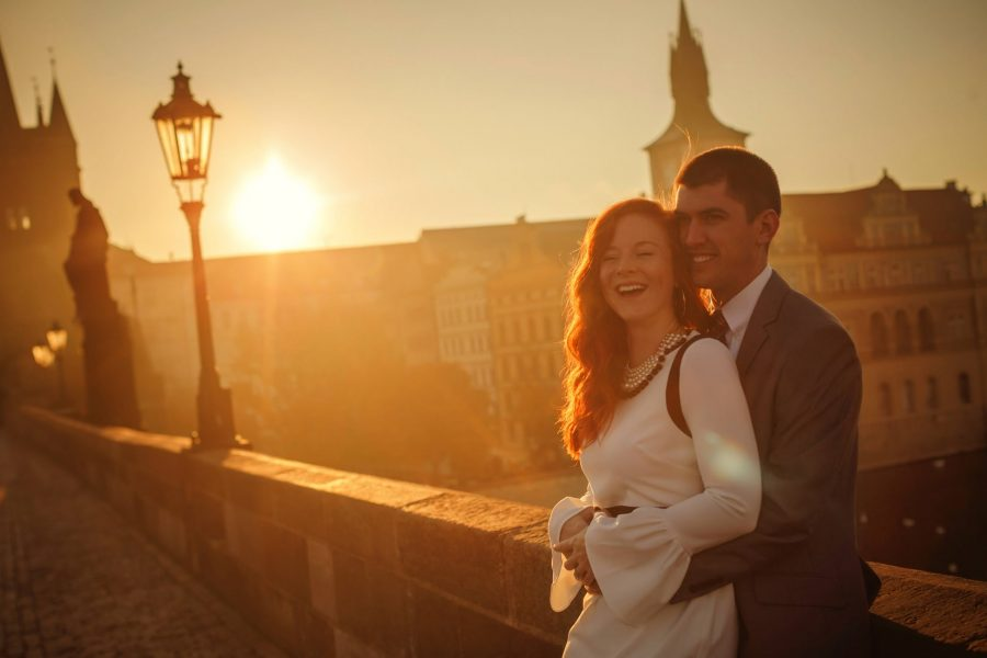 Prague Charles Bridge sunrise, Golden & Orange color, sun flare, smiling couple, street lamp