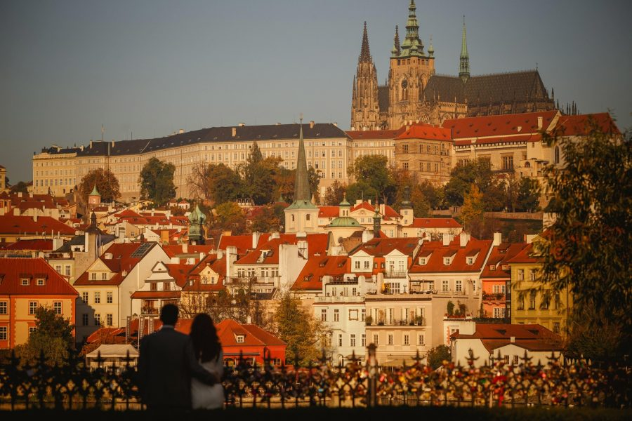 Prague Castle, silhouette, well dressed couple embracing, love locks, color orange