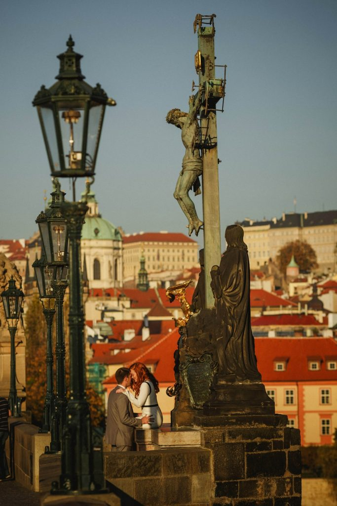 Prague Charles Bridge, iconic statues, religious motif, well dressed couple embracing, sunshine