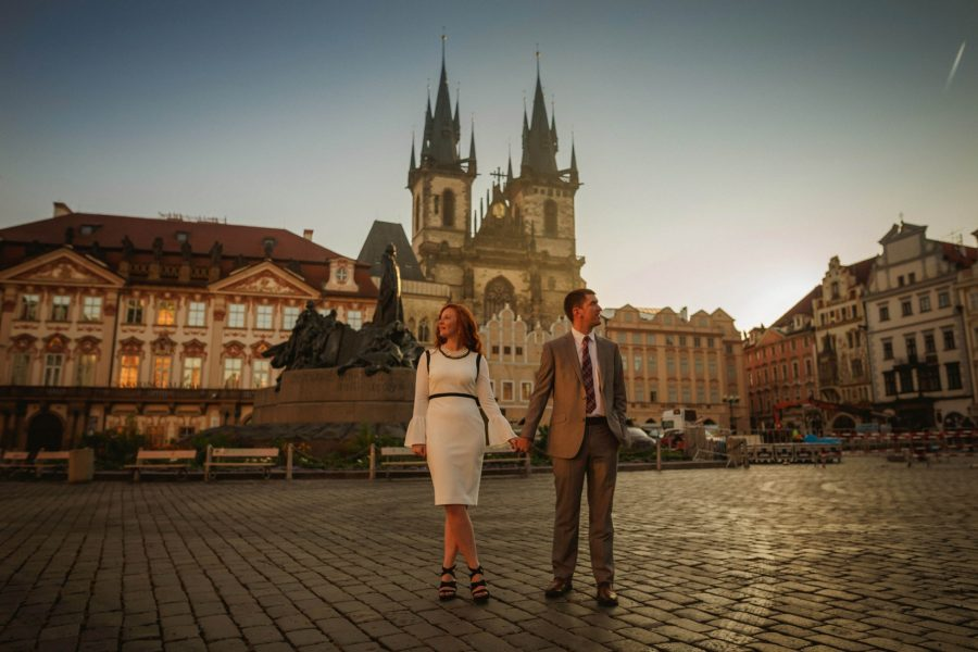 Prague Old Town Square, well dressed couple holding hands looking around, Tyn Church