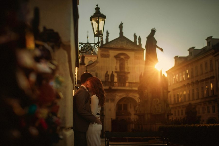 Prague, well dressed couple embracing, love locks, sun flare, statue