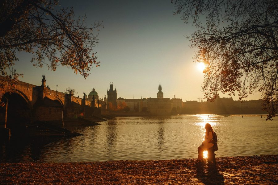 Prague, well dressed couple sitting, sun flare over river, Charles Bridge