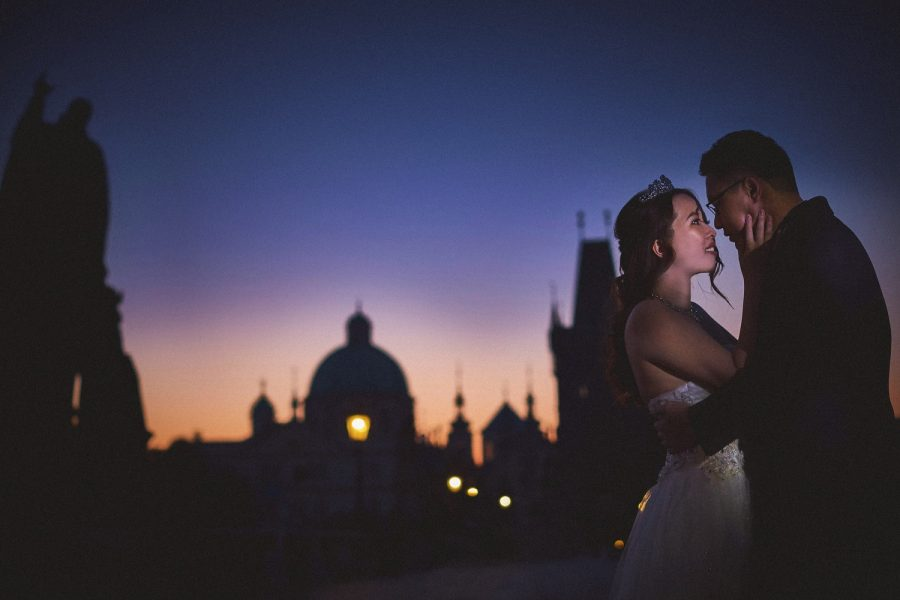 Charles Bridge at night, couple embracing, wedding dress, blue & pink sky, gas lamps