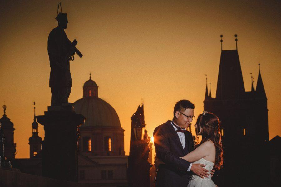 Prague, Charles Bridge sunrise, couple embracing, wedding dress, yellow sky, sun flare, statues