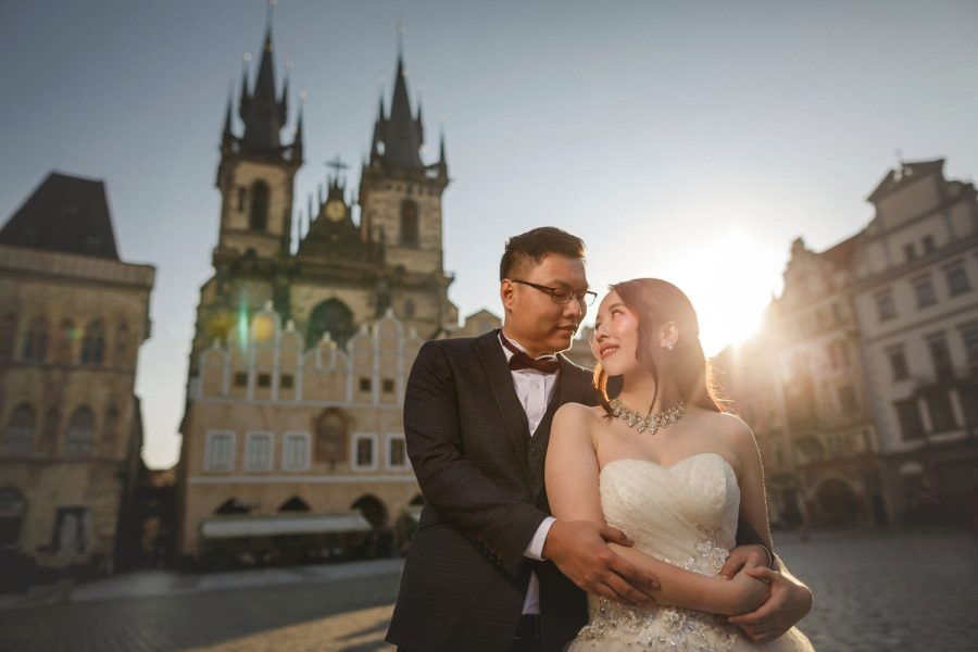 Prague Old Town Square, wedding couple embracing, Tyn Church, sun flare