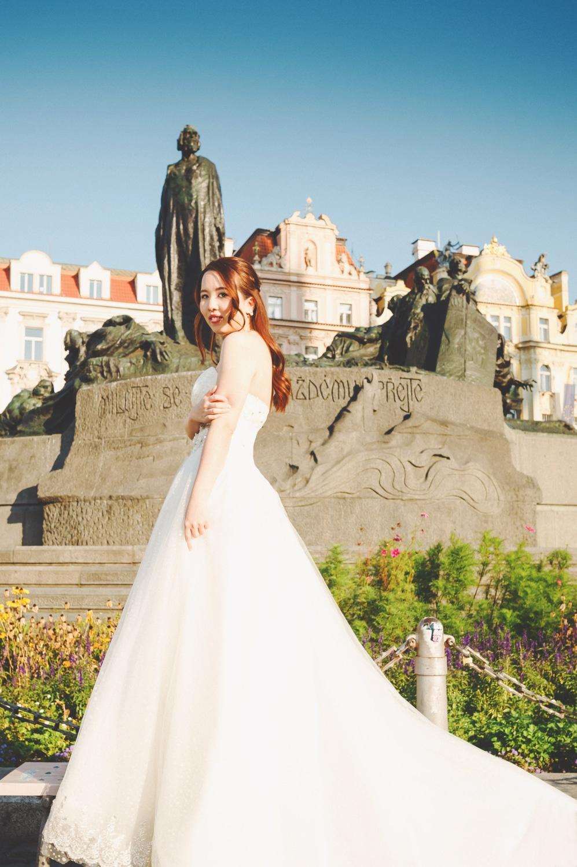Prague Old Town Square, vintage bridal portrait, wedding dress, blue sky, statues