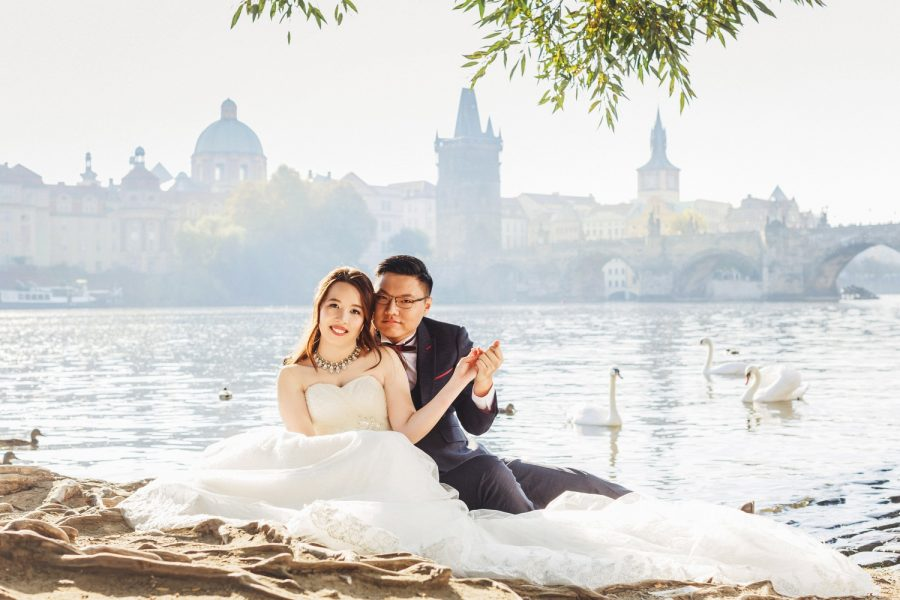 Prague riverside, wedding couple sitting, holding hands, swans, Charles Bridge