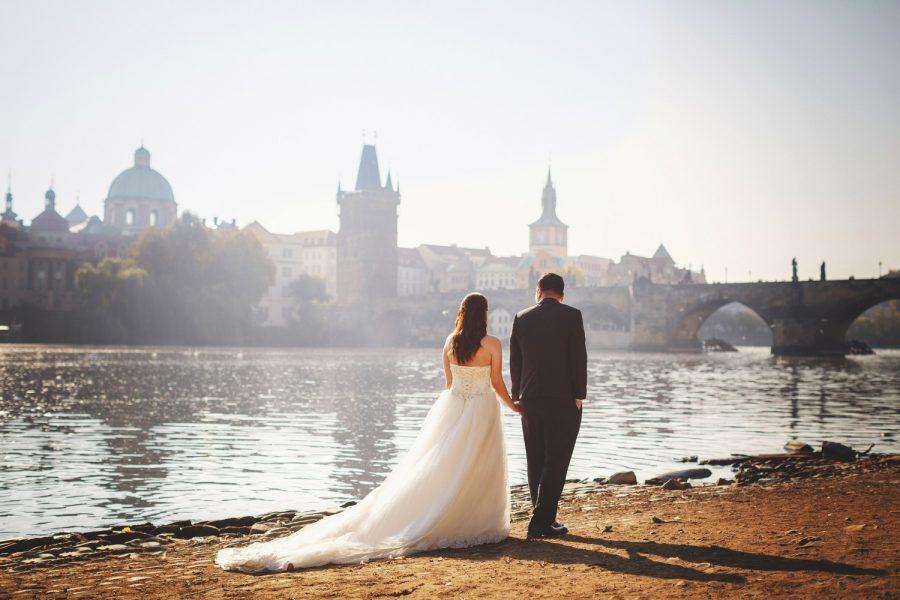 Prague riverside, wedding couple walking, holding hands, Charles Bridge, swans