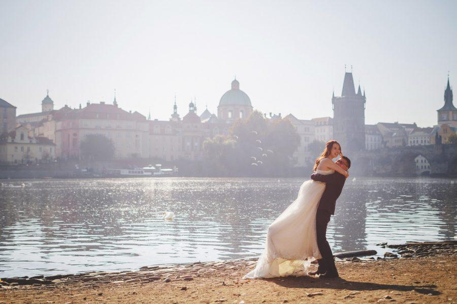 Prague riverside, wedding couple embracing, Charles Bridge, swans