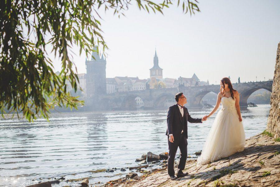 Prague riverside, wedding couple walking holding hands, Charles Bridge, swans