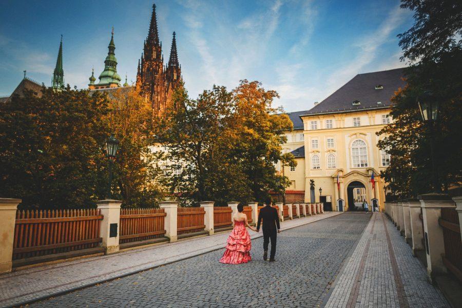 Prague Castle, young couple walking hand in hand, castle guard shacks, St. Vitus, blue sky