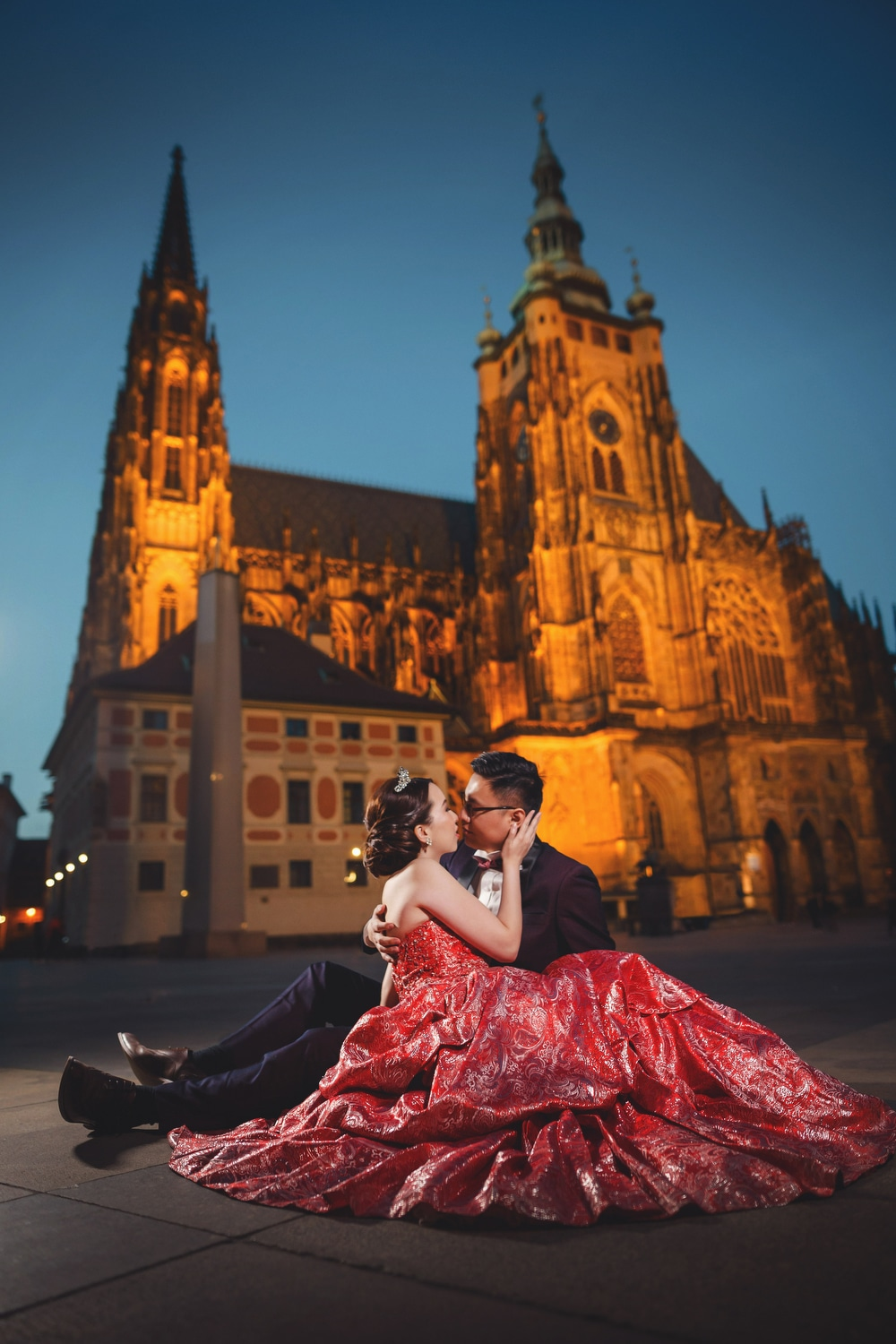 Prague Castle, young couple sitting, embracing, red dress, night image, St. Vitus, blue sky