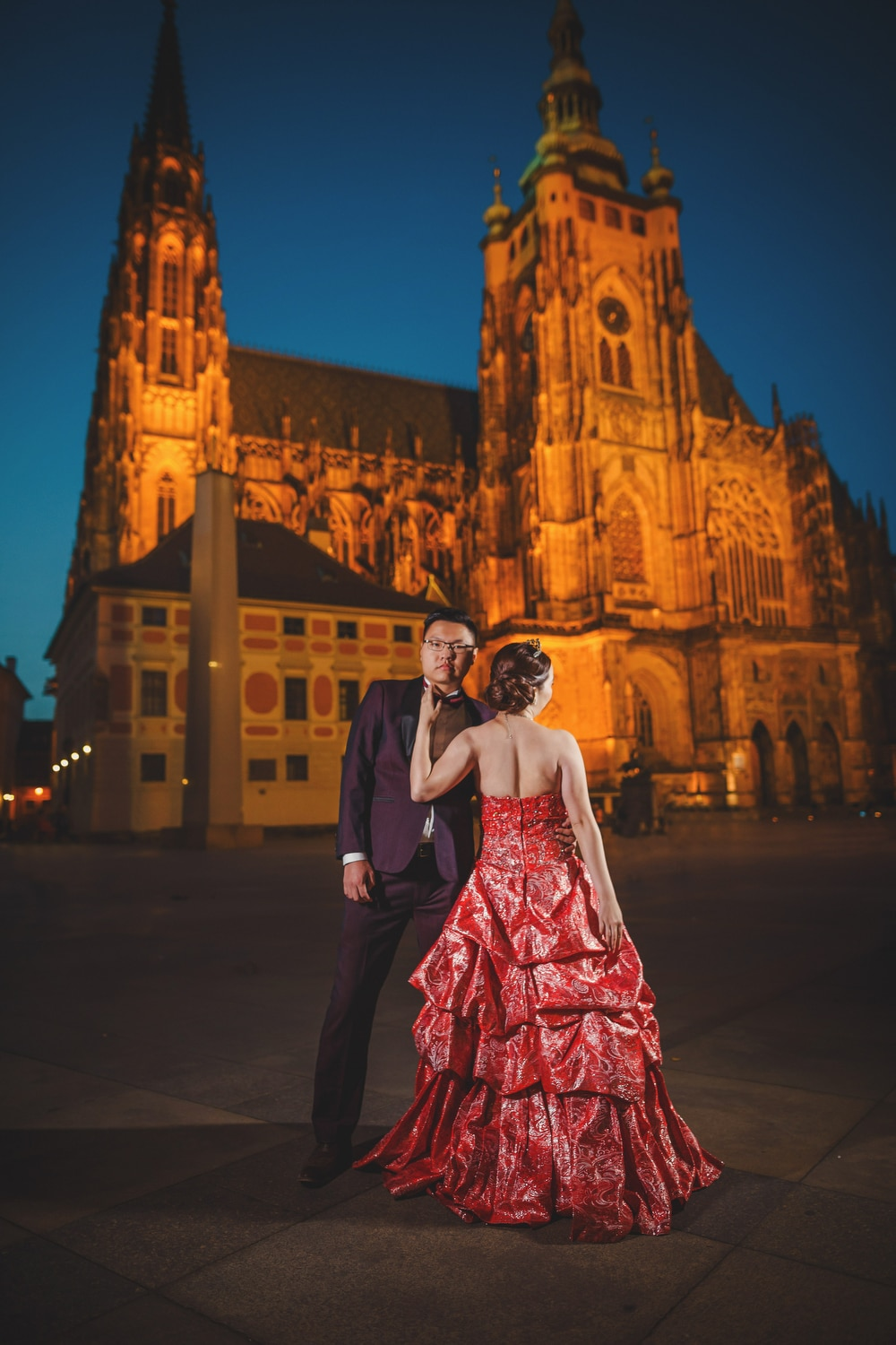 Prague Castle, young couple standing, red dress, night image, St. Vitus, blue sky