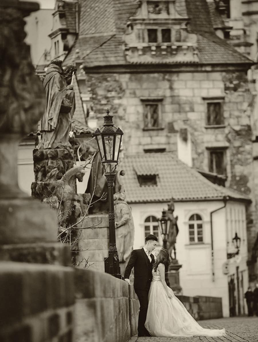 A B&W photo captured at the Charles Bridge in Prague - a Love Story Engagement photo shoot with Tina & Mike