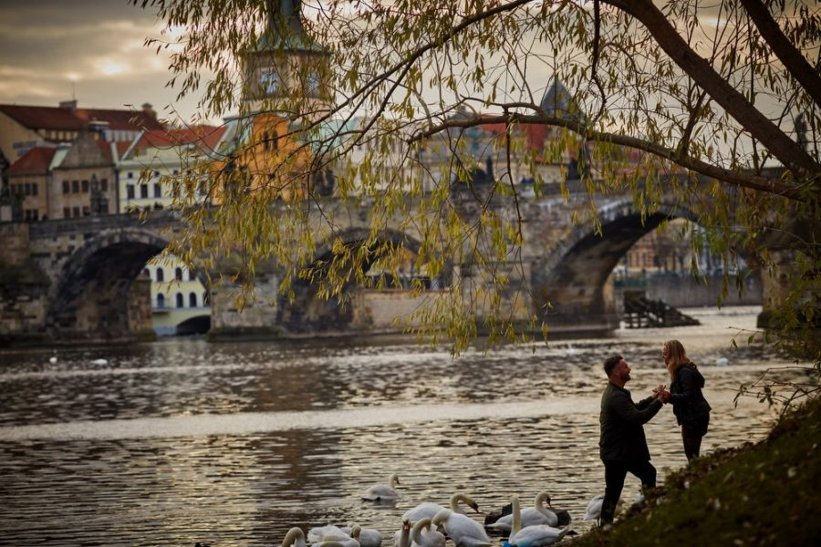 Enjoying the view of the Charles Bridge from the riverside during their lifestyle photo session