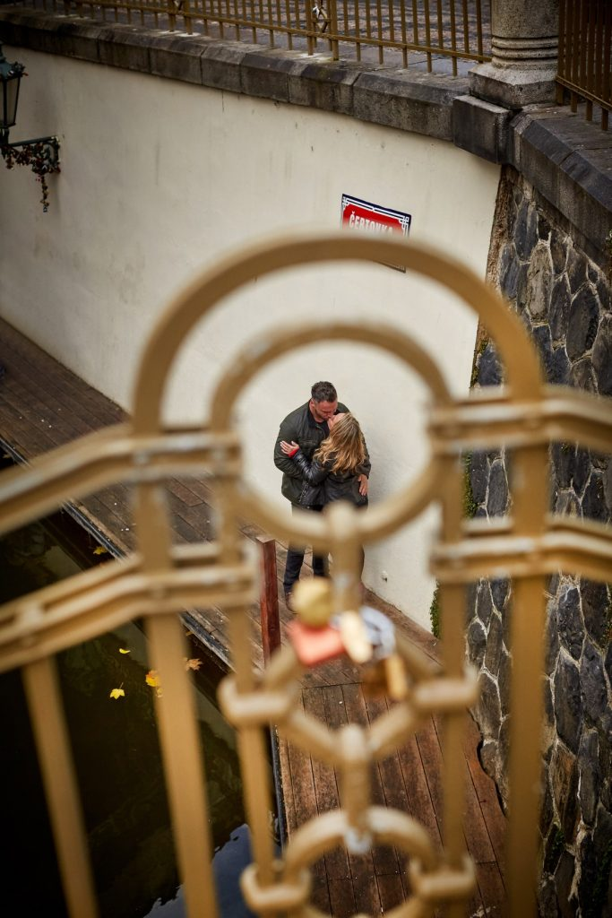 The wrought iron fence provides the framing for our couple who were enjoying Prague's little Venice
