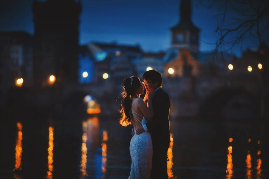 An early morning embrace during their riverside photo session with the Charles Bridge in the background.