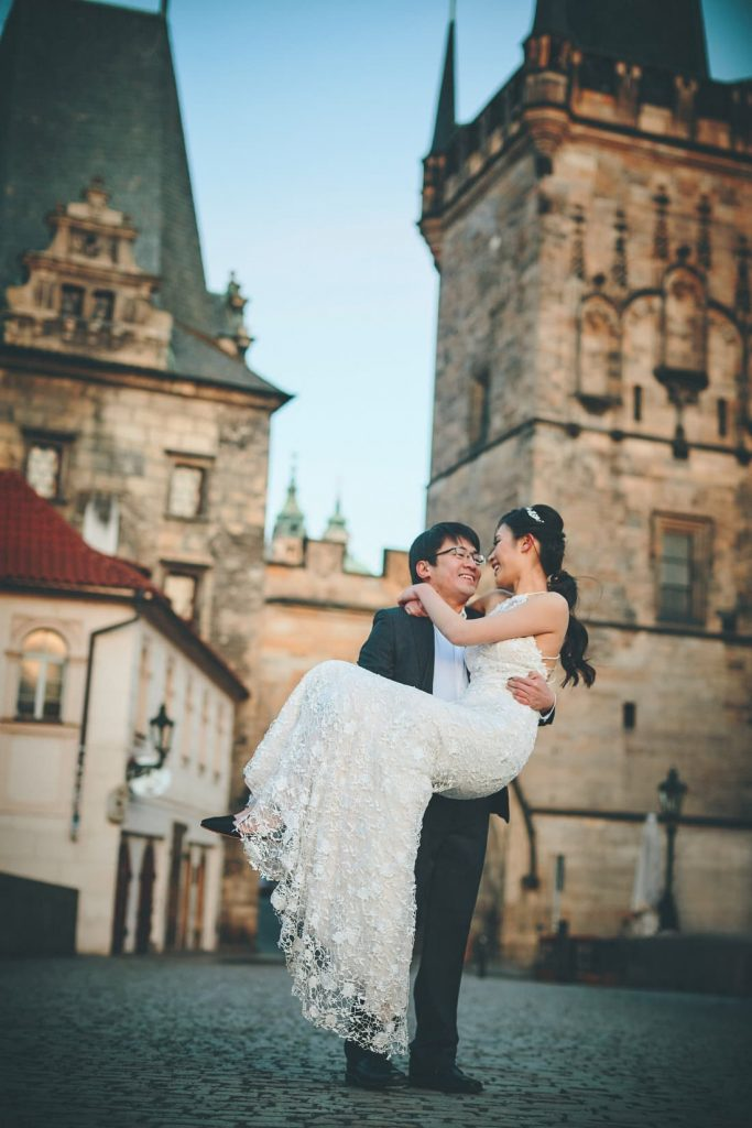 Timmy carries Joyce aloft in her wedding dress during the sunrise part of their Charles Bridge portrait session.