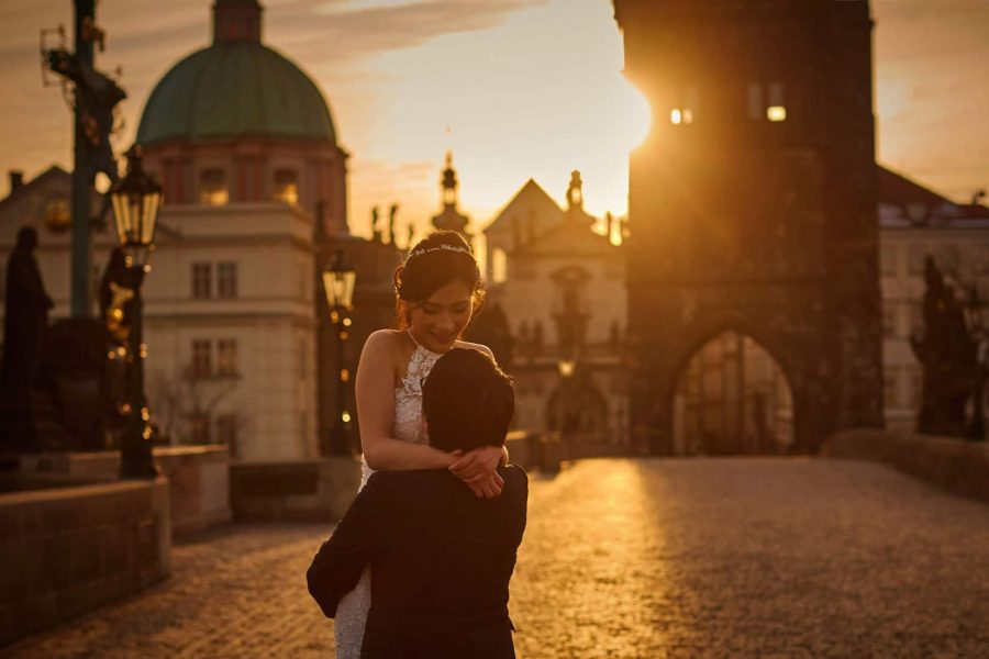 Nothing more beautiful than a couple dressed in their wedding clothes having a real moment as the sun flares above them on the Charles Bridge.