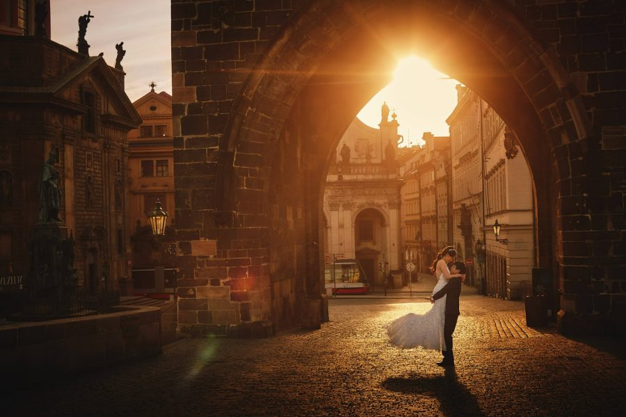 One of the most beautiful, iconic photos: a young bride in her wedding attire is spun around as the sun flares through the Powder Tower of the Charles Bridge.
